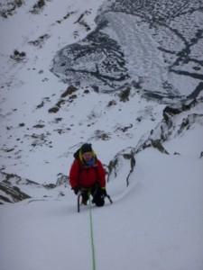 Richard High on V Corner, a frozen Red Tarn far below.